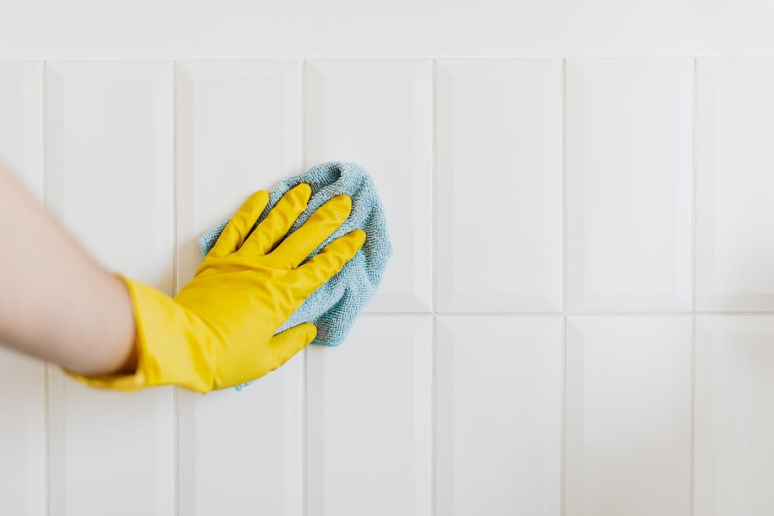 A person wearing yellow gloves and cleaning a wall with a rag