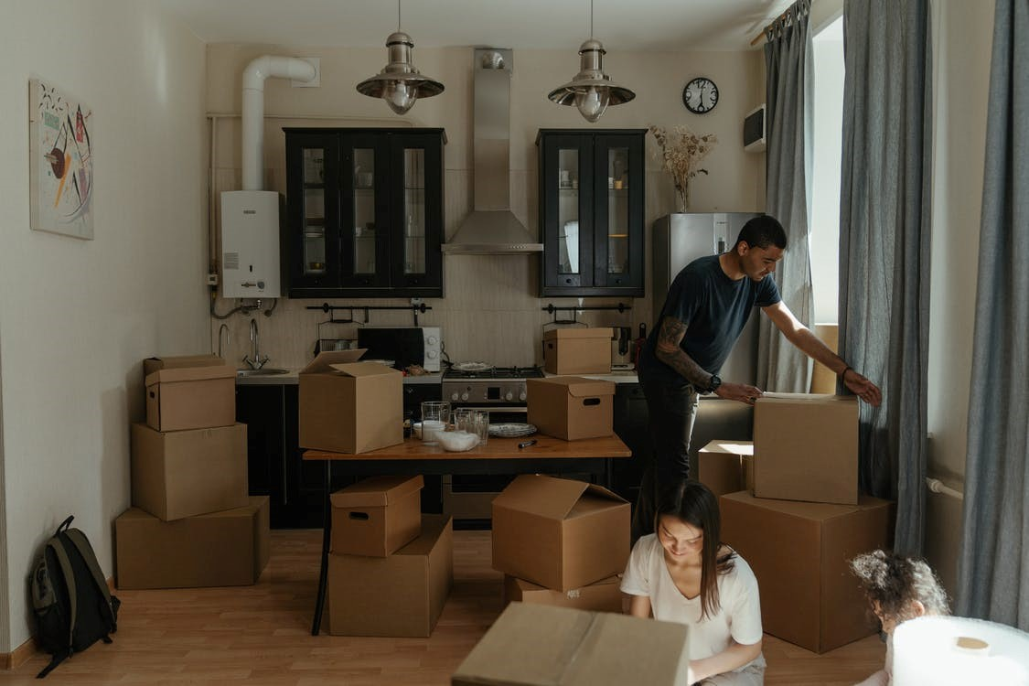 A couple unpacking their cardboard boxes in a new home
