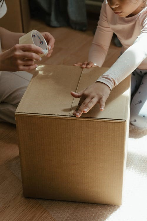 Professional movers service helping you carefully tape boxes in a house in Seattle.