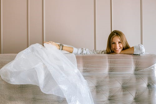 A woman uncovering a plastic headboard in a new apartment.