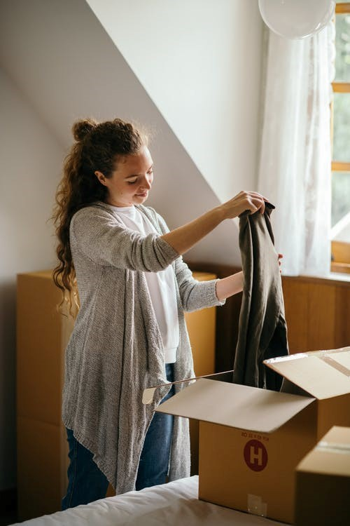A woman packing clothes for a move.