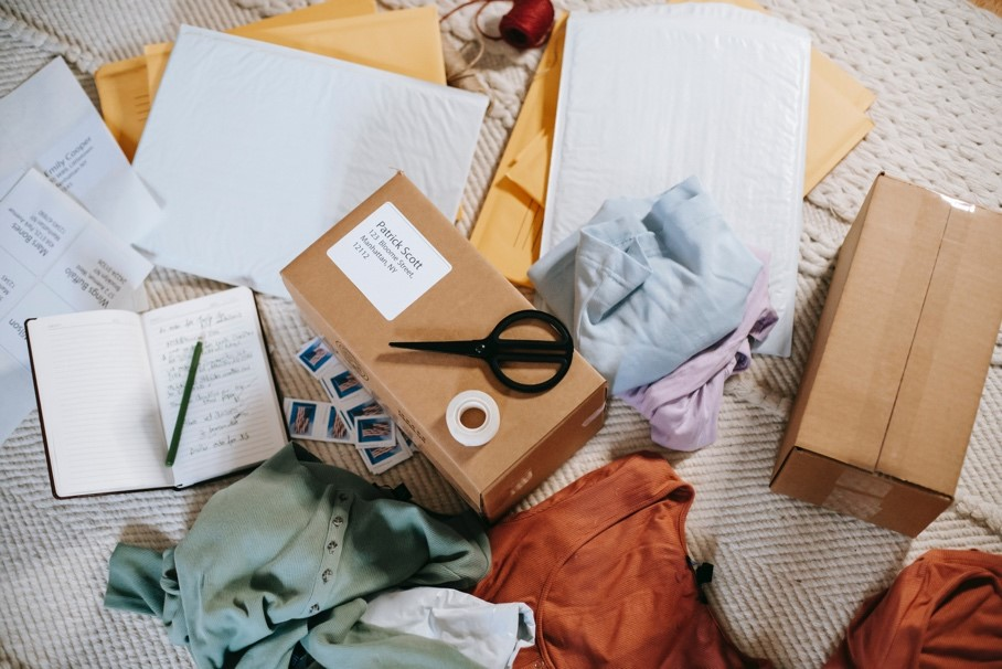 An assortment of clothes, boxes, lists, and other things being organized