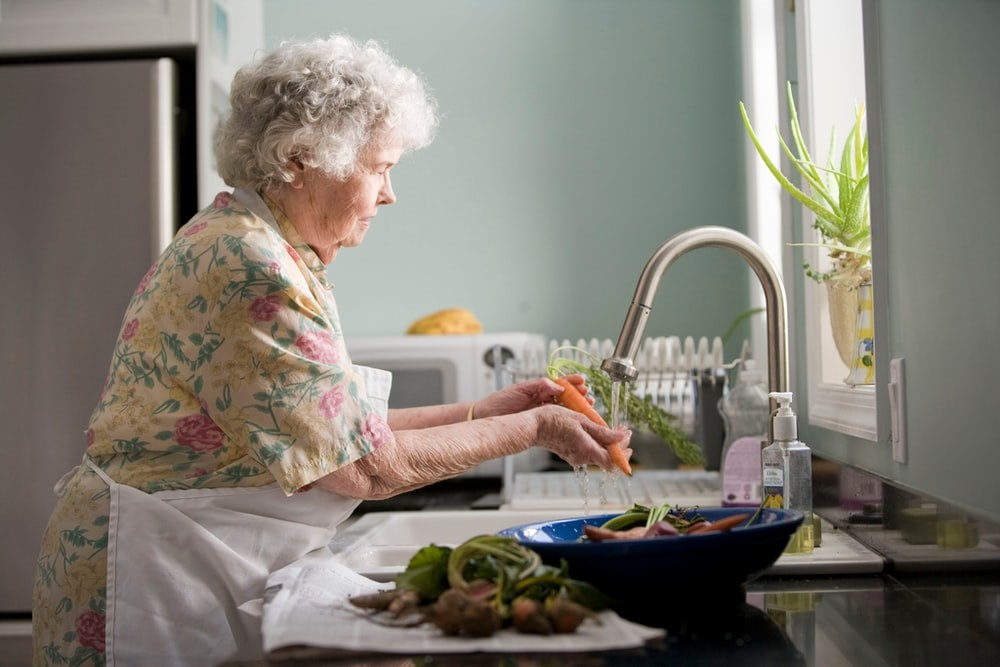 An older woman is watching the vegetables.