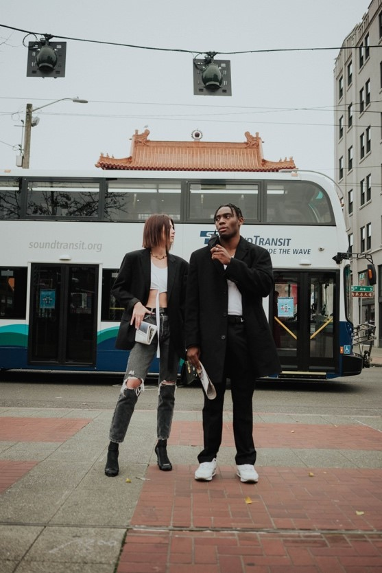 Two tourists standing in front of a Sound Transit bus in Seattle