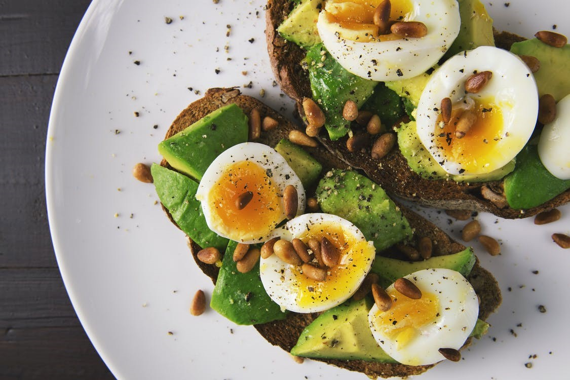 Boiled eggs with avocado on a loaf of wholegrain bread.