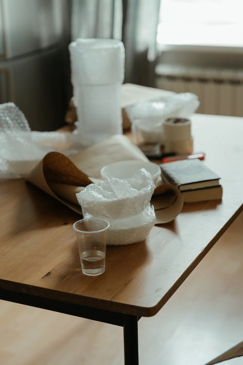 White ceramic mugs in bubble wrap on a wooden table