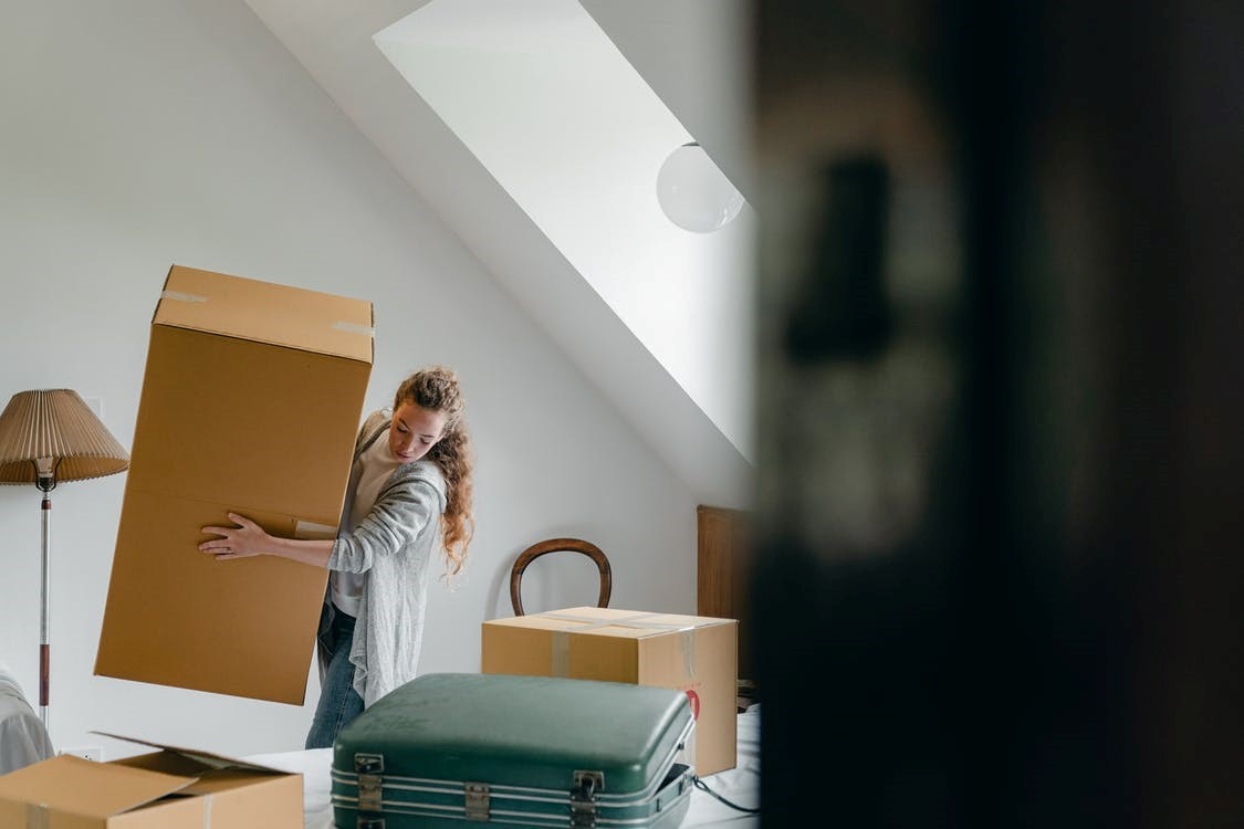 A woman carrying a packed brown cardboard box in her new house