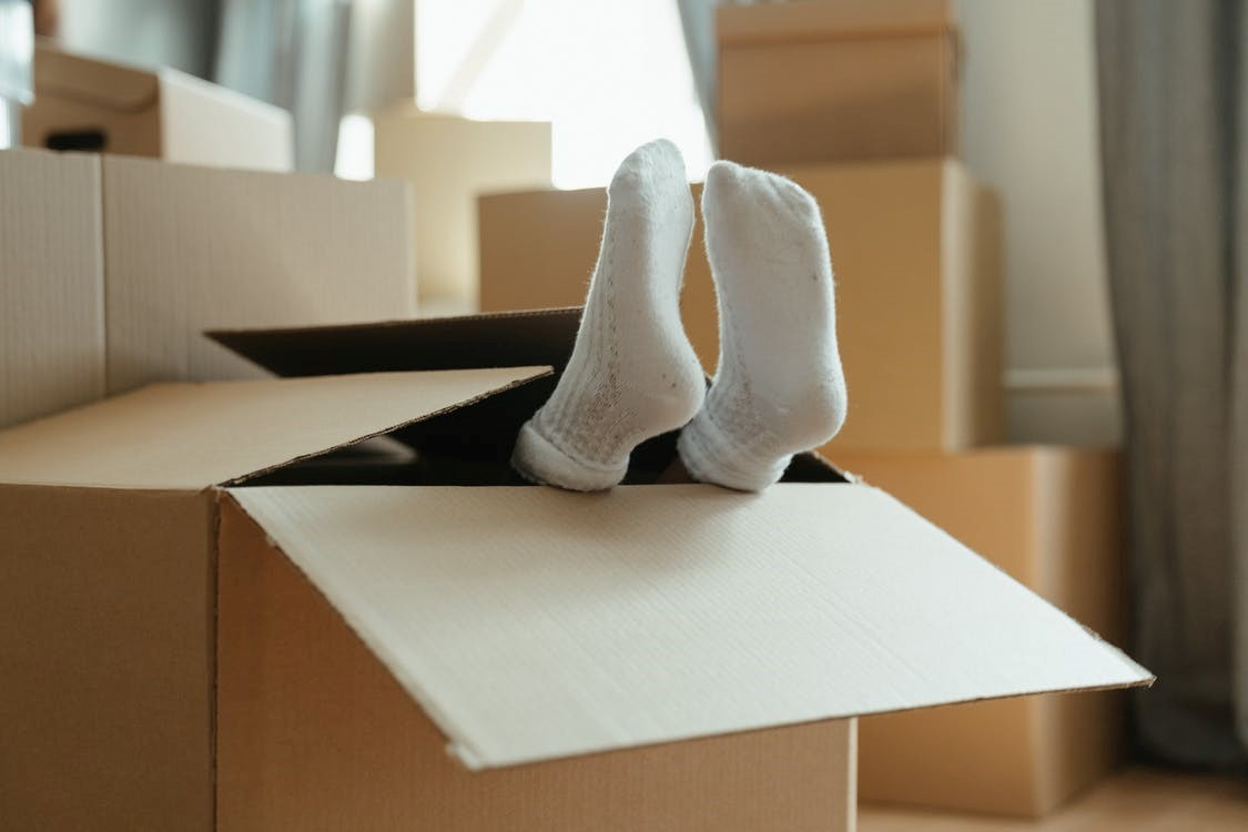 A child with white socks in a brown cardboard box