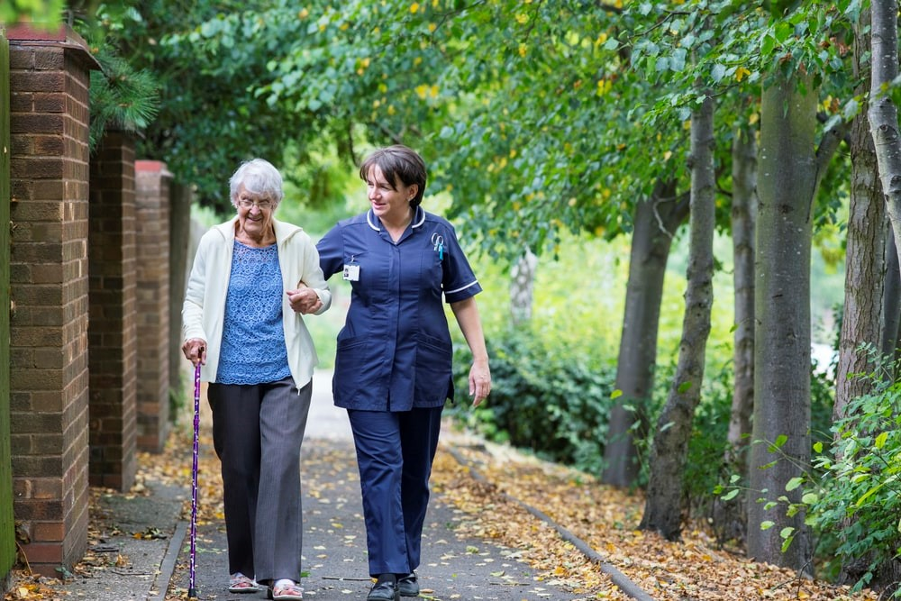 A nurse is supporting an older woman while she walks.