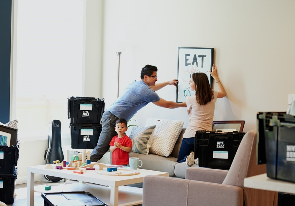 A couple is seen decorating the room with their young boy.