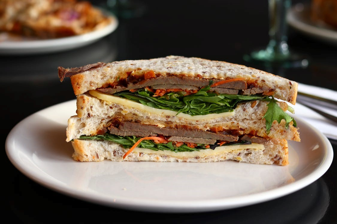 A healthy sandwich with vegetables and meat on a plate.