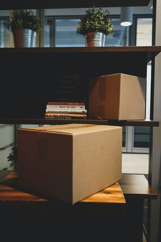 Unpacked boxes placed on a bookshelf