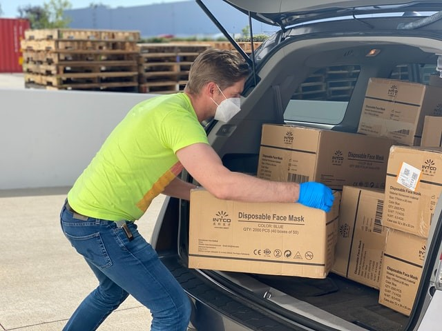 A person with a mask and gloves puts boxes in the trunk