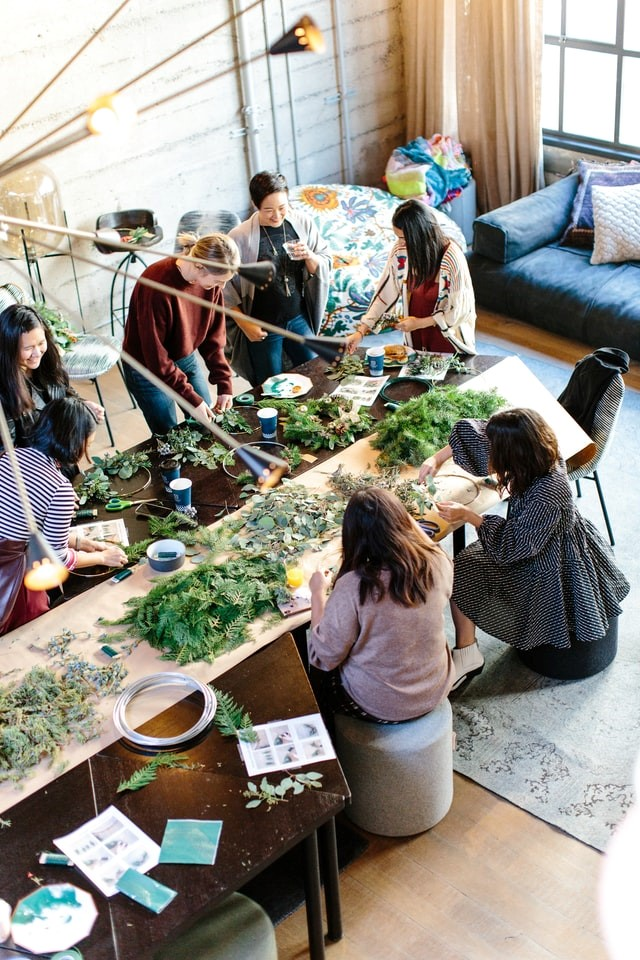 A group of women participating in a flower pressing activity