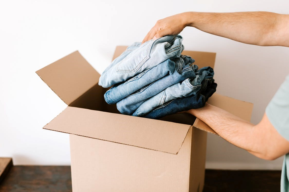 A man placing blue jeans inside a cardboard box