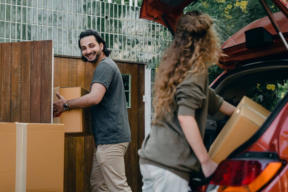 A happy couple unloading their packed boxes from their car