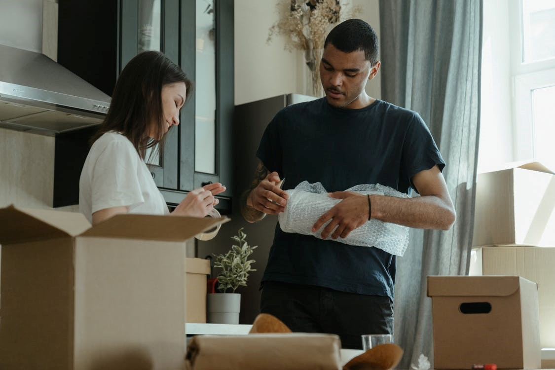 A couple unpacking boxes in a kitchen in their new home