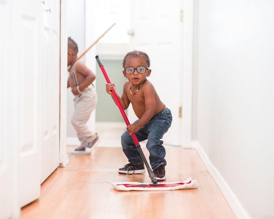 A tween boy is seen sweeping the floor.
