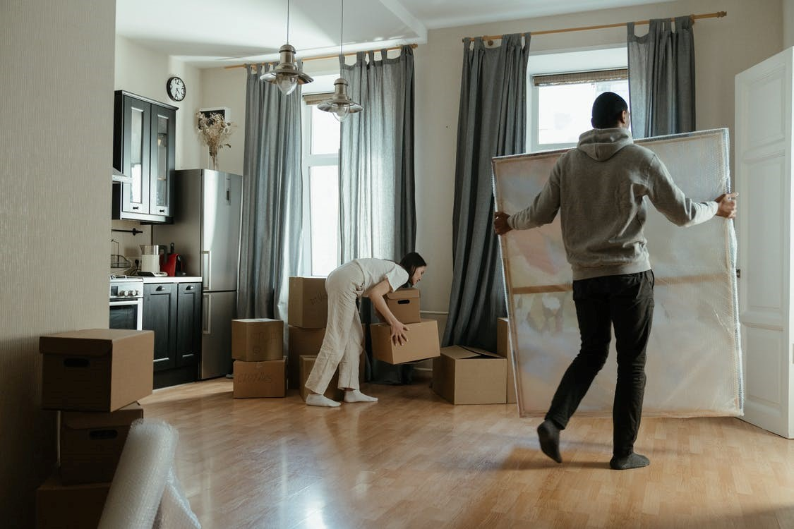 A couple can be seen arranging furniture in the lounge.