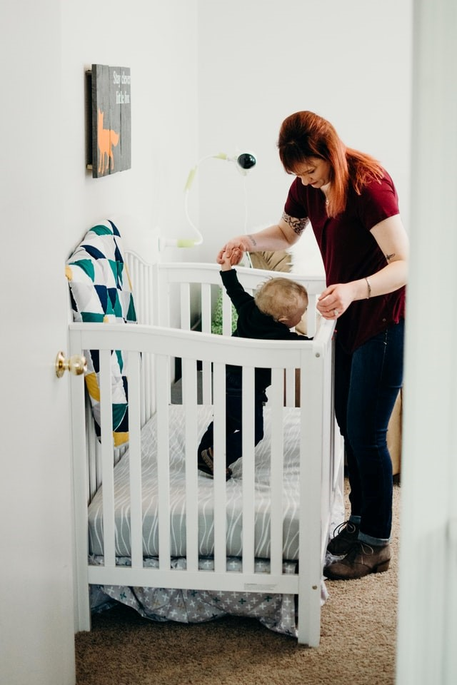 A woman with a baby in their nursery
