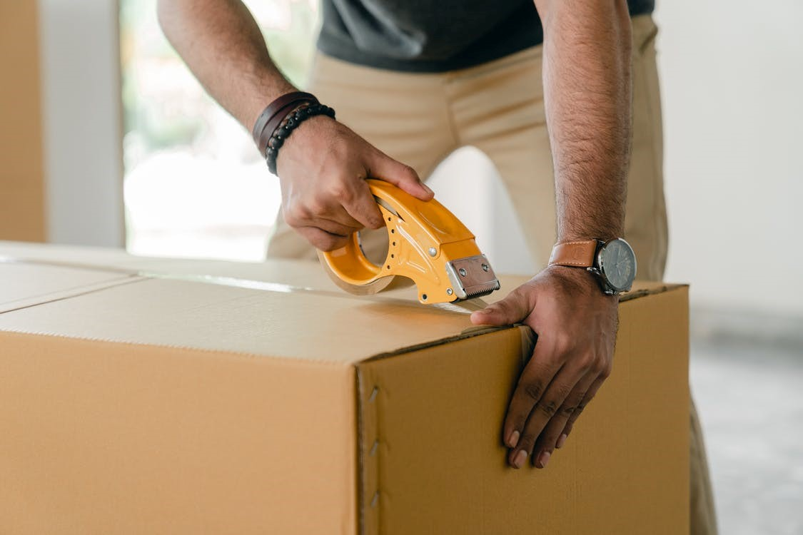 Professional mover packing brown box