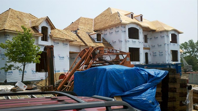 A work in progress of a new roof being installed on a new construction home.