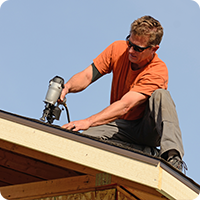 A Naperville roofer installing shingles on a roof.