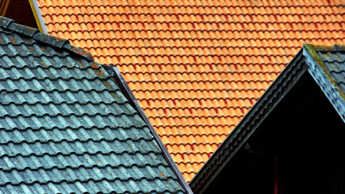 A photo of brown and blue tiles on home roofs. Photo by Boris Misevic on Unsplash