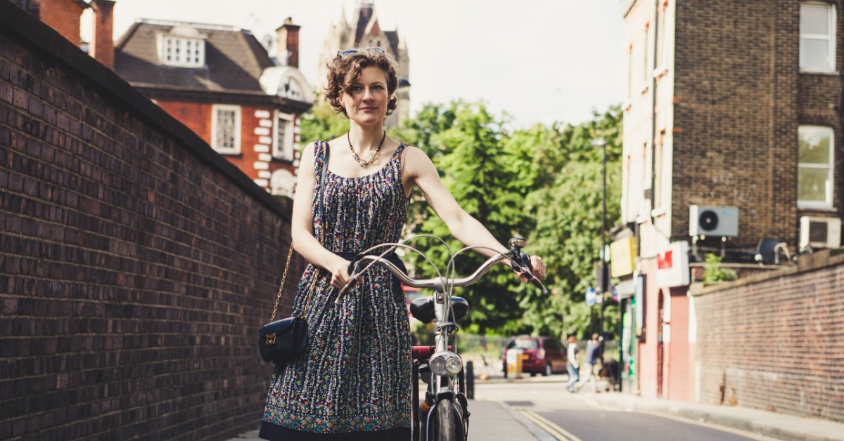 Confident woman standing next to a bicycle in a city setting.