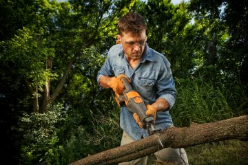 man sawing tree branch in autumn, as we suggest at Advanced Landscape & Sprinkler Inc