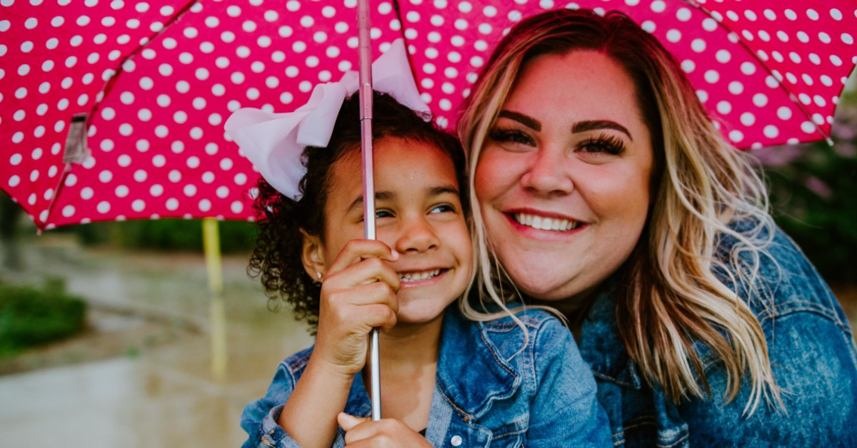 smiling faces of a woman and young girl holding an umbrella