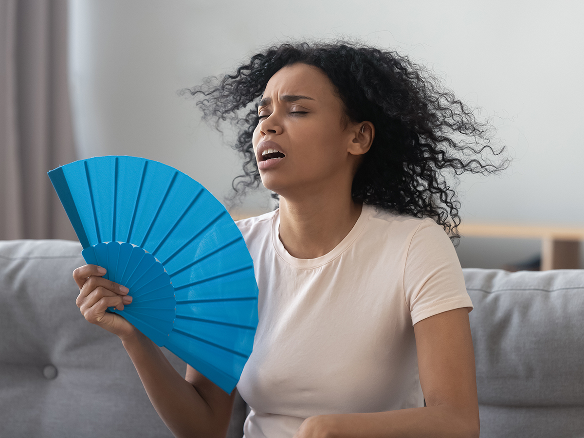 Woman cooling herself with a handheld fan because her AC doesn't work well.