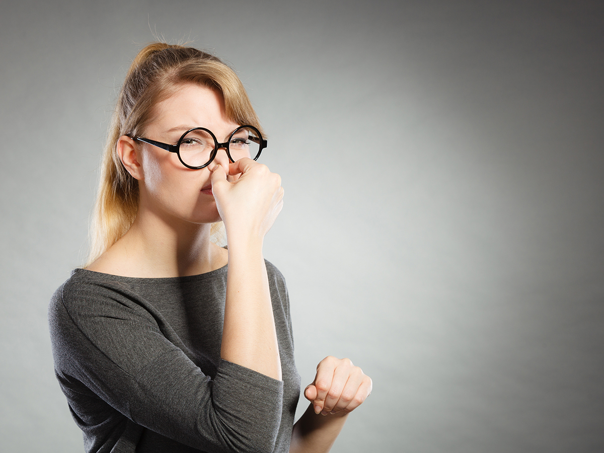Young woman plugging her nose.