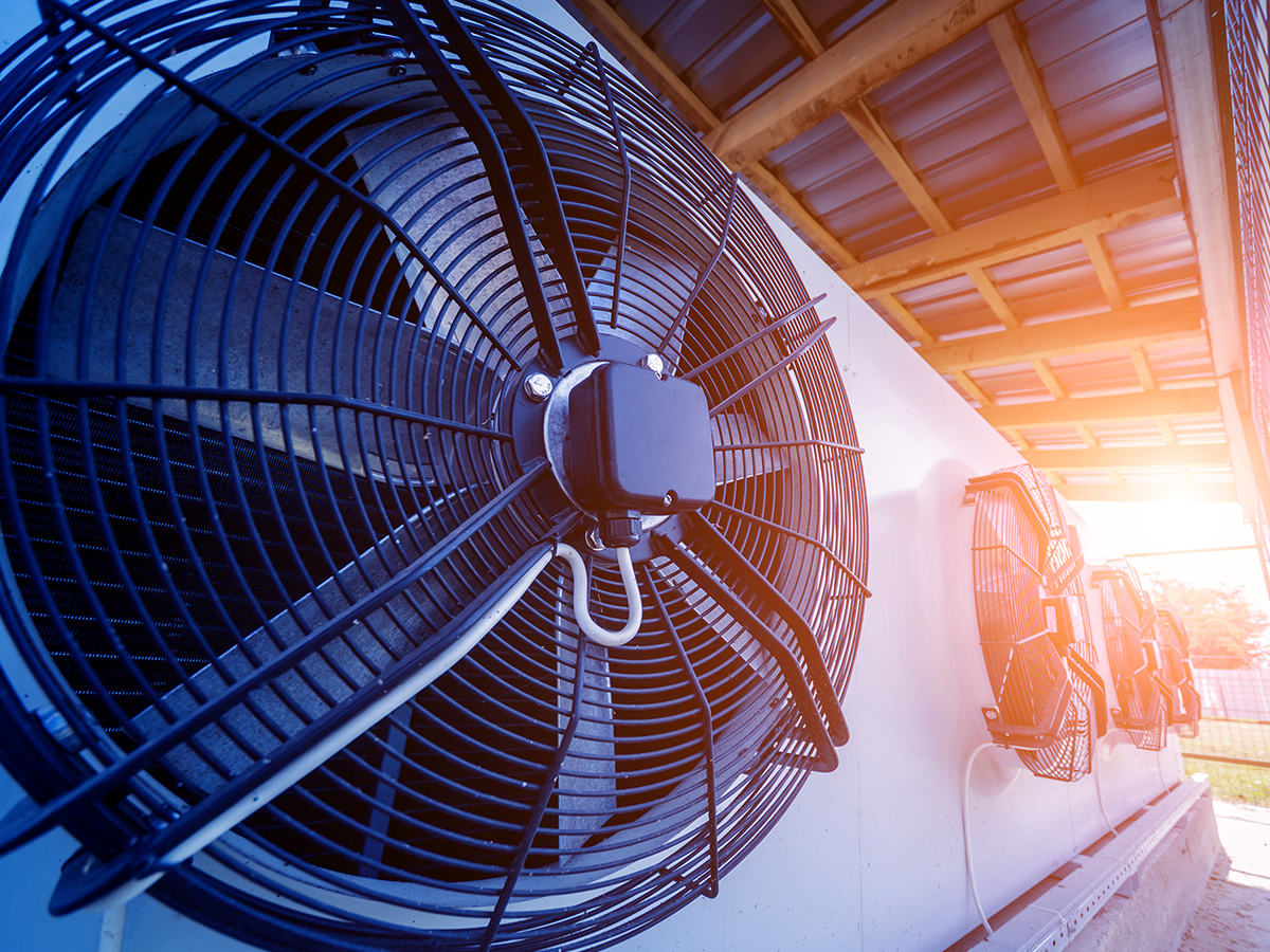 Four large industrial HVAC fans sitting with the glow of a sunset in the distance.