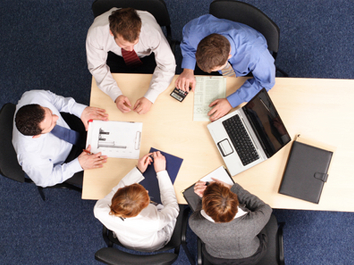 OVerhead view of five employees in business attire sitting at a table working together.