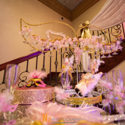 A close-up shot of a beautifully decorated table lit by purple lighting at Alegria Gardens Reception Hall in Houston.