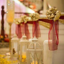 Lit lanters with rose petals next to decorated chairs inside of Alegria Gardens Reception Hall in Houston.