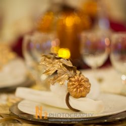Wrapped silverware with a golden pumpkin and leaf on top.