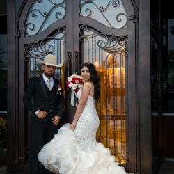 A bride holding a bouquet of flowers standing next to a groom wearing a cowboy hat at Alegria Gardens Reception Hall in Houston.