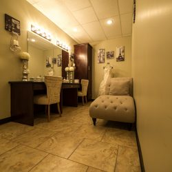 A photo of Alegria Gardens Reception Hall's well-lit dressing room with large mirrors, two chairs, and a bench.