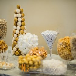 A beautiful dessert table with white and gold pretzels, candy, cake pops, and macarons at Alegria Gardens Reception Hall in Houston.