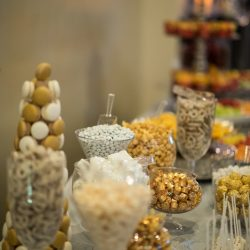 Dessert table featuring candy, cake pops, macarons, and coated pretzels at Alegria Gardens Reception Hall in Houston.