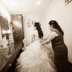 A picture of a bride getting into her dress before a wedding at Alegria Gardens Reception Hall in Houston.