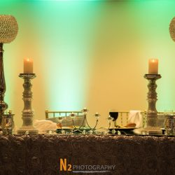 Table with ornate candles, wine glasses, and a rose petal table cloth at Alegria Gardens Reception Hall in Houston.