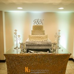 Cake with white rose petals on top of a sparkling table cloth at Alegria Gardens Reception Hall in Houston.