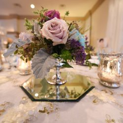 Pink rose with assorted flowers on top of a white and gold tablecloth at Alegria Gardens Reception Hall in Houston.
