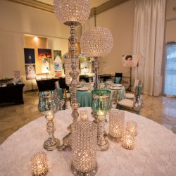 Ornate candles on top of a rose petal table cloth inside of Alegria Gardens Reception Hall in Houston.