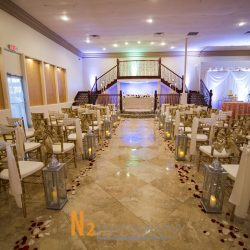 Wedding ceremony area with decorated tables, candles, and rose petals inside of Alegria Gardens Reception Hall in Houston.