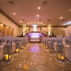 White chairs, rose petals, and candles for a wedding inside of of Alegria Gardens Reception Hall in Houston.