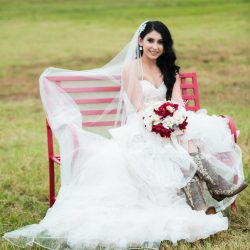 Bridge wearing a white dress and carrying flowers outside of Alegria Gardens Reception Hall in Houston.